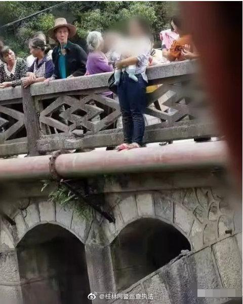站在高尚大桥外、怀抱小孩的女子,被民警救下